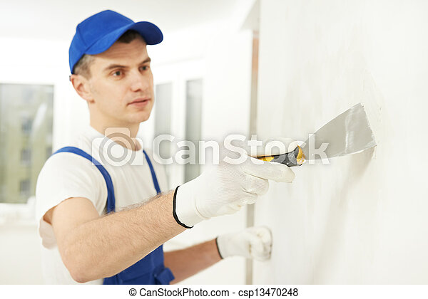 Plasterer with putty knife at wall filling - csp13470248