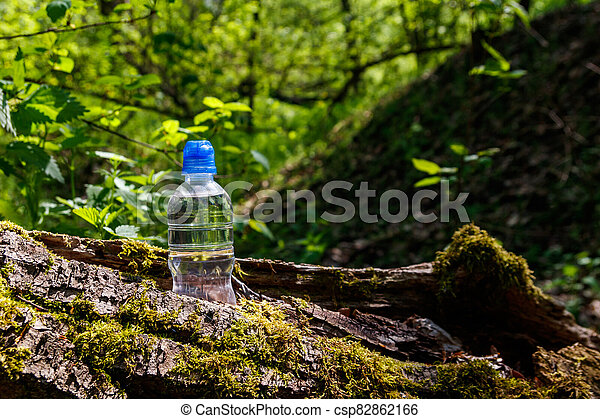 Plastic bottle with fresh drinking water on green forest background - csp82862166