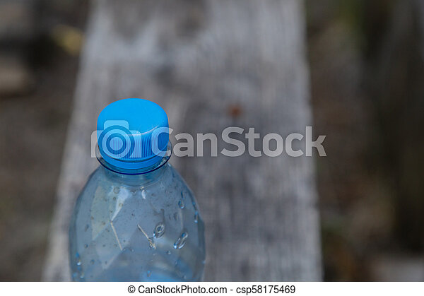 Plastic bottle with water on a wooden background. - csp58175469