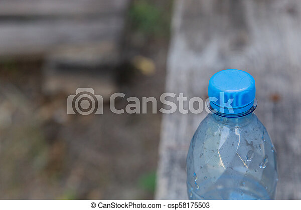 Plastic bottle with water on a wooden background. - csp58175503
