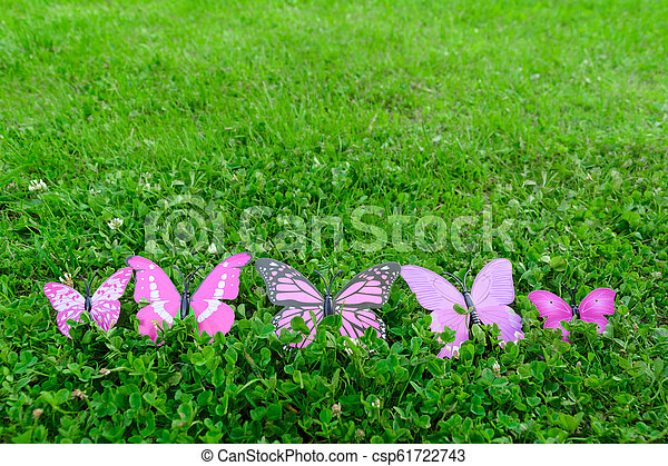 Plastic butterfly on green grass with copy space - csp61722743