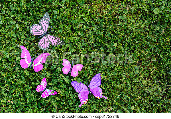 Plastic butterfly on green grass with copy space - csp61722746