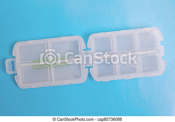 Plastic container for pills on blue background - csp80736088