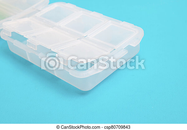 Plastic container for pills on blue background - csp80709843