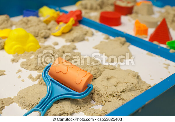Plastic Mold toys with sand on sandbox. Background blurry. - csp53825403
