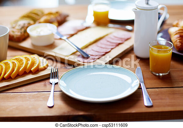 plate and glass of orange juice on table with food - csp53111609