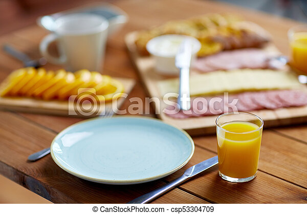 plate and glass of orange juice on table with food - csp53304709