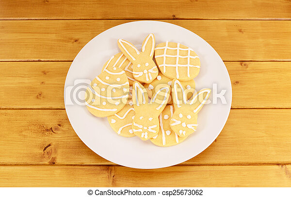 Plate full of frosted Easter cookies on a wooden table - csp25673062