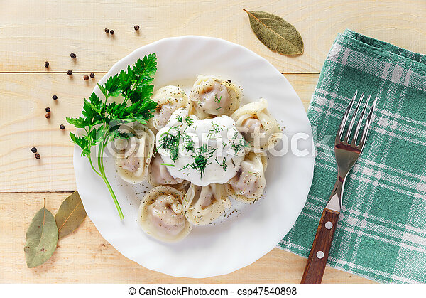 Plate with boiled dumplings served with parsley and sour cream - csp47540898