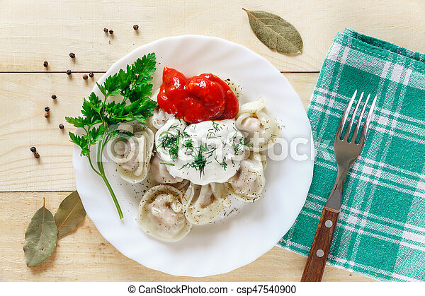 Plate with boiled dumplings served with parsley and sour cream - csp47540900