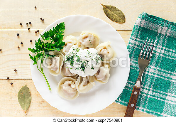 Plate with boiled dumplings served with parsley and sour cream - csp47540901