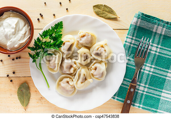 Plate with boiled dumplings served with parsley and sour cream - csp47543838