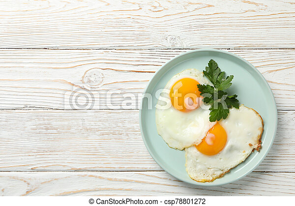 Plate with fried eggs on wooden background, top view - csp78801272