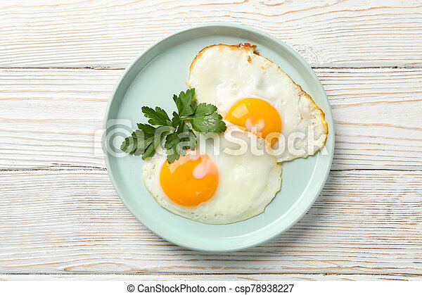 Plate with fried eggs on wooden background, top view - csp78938227
