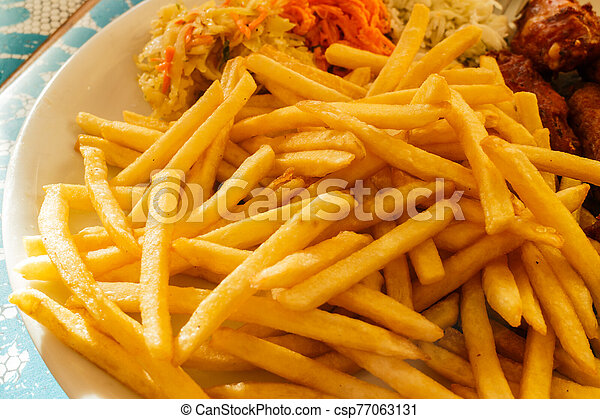 Plate with meal, chips, chicken wings and salad - csp77063131