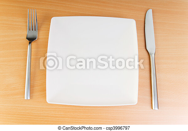 Plate with utensils on wooden table - csp3996797