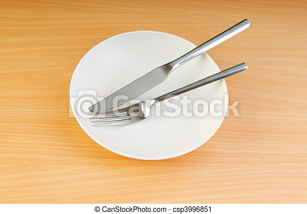 Plate with utensils on wooden table - csp3996851