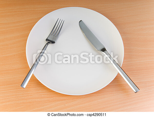 Plate with utensils on wooden table - csp4290511