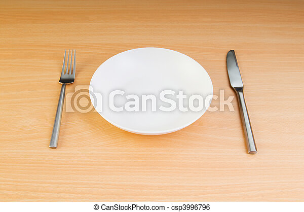 Plate with utensils on wooden table - csp3996796