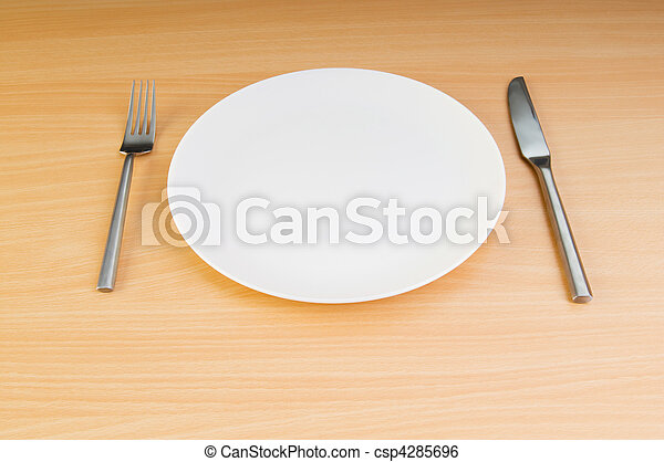 Plate with utensils on wooden table - csp4285696