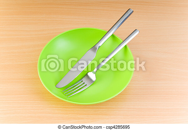 Plate with utensils on wooden table - csp4285695