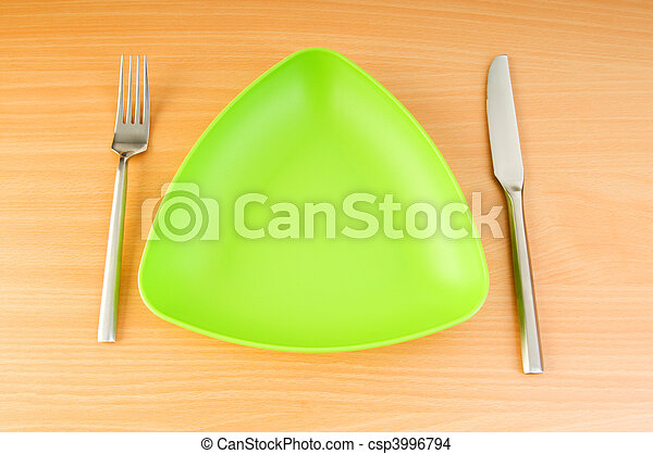 Plate with utensils on wooden table - csp3996794