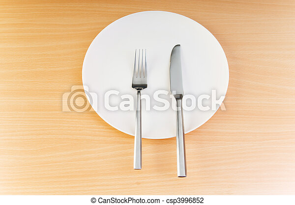 Plate with utensils on wooden table - csp3996852