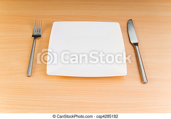 Plate with utensils on wooden table - csp4285182