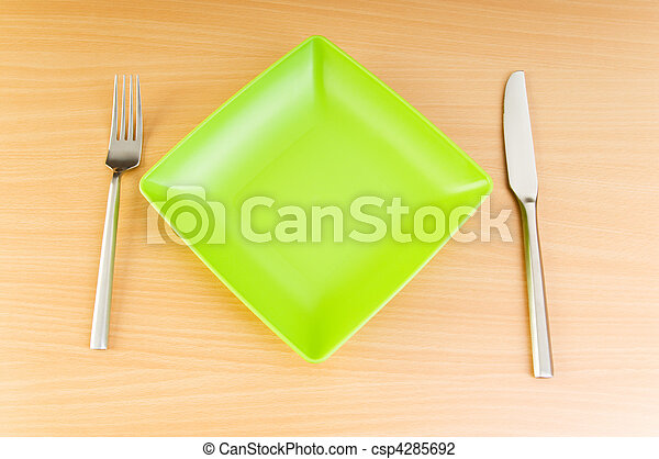 Plate with utensils on wooden table - csp4285692