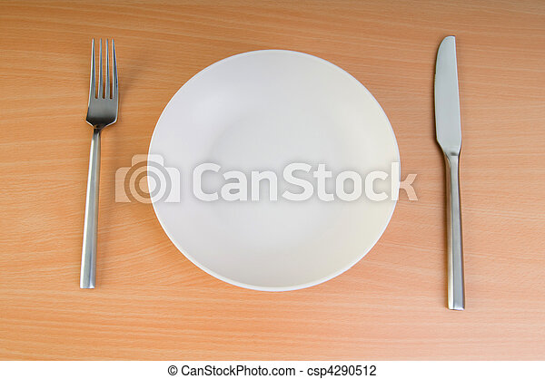 Plate with utensils on wooden table - csp4290512