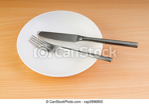 Plate with utensils on wooden table - csp3996850