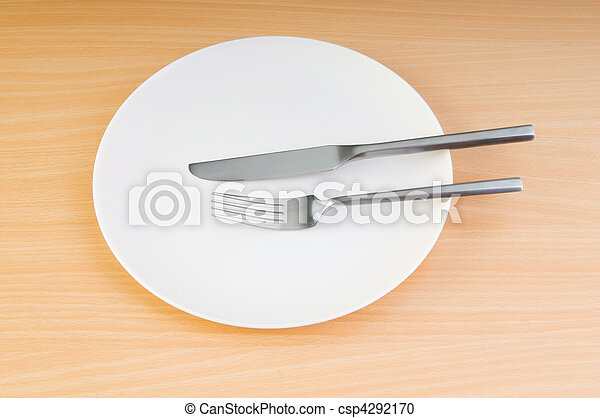 Plate with utensils on wooden table - csp4292170