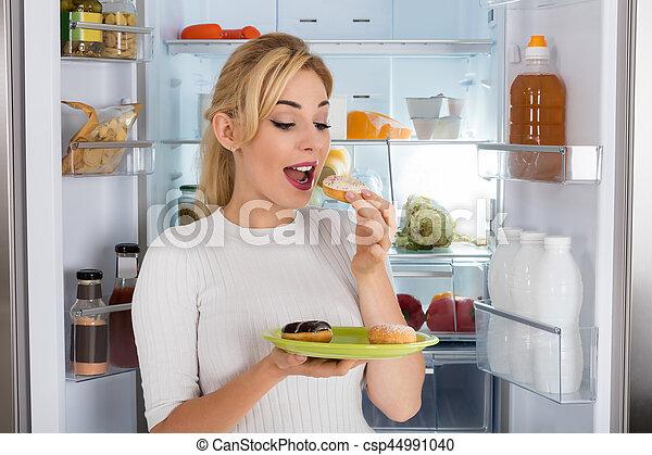 Kühlschrank Platte : Stehende platte frau essen junger donut kühlschrank.