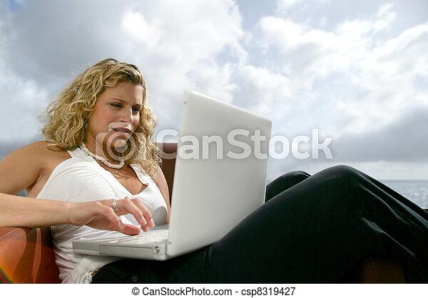 Una mujer se sentó en la playa con una laptop - csp8319427