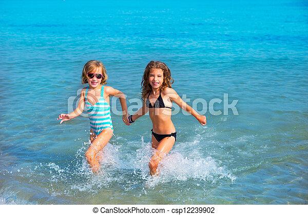 Niñas amigas corren juntas en la playa - csp12239902