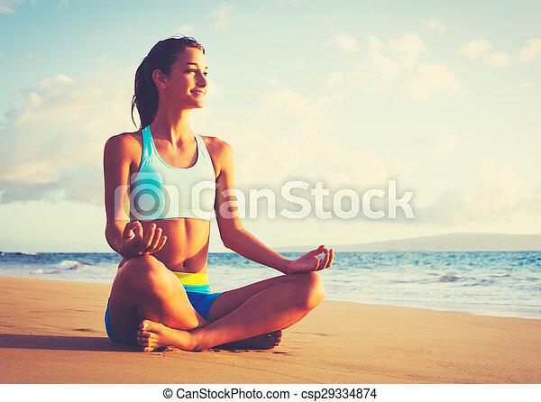 Mujer practicando yoga en la playa al atardecer - csp29334874