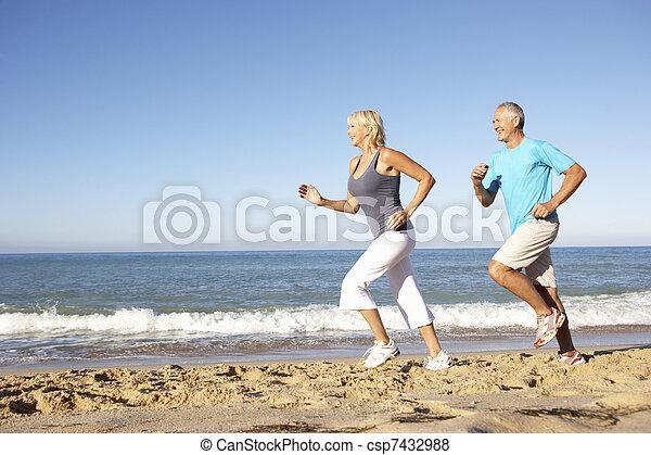 Pareja mayor con ropa de gimnasia corriendo por la playa - csp7432988