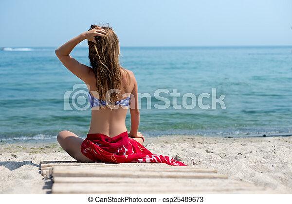 Una mujer camina por la playa - csp25489673