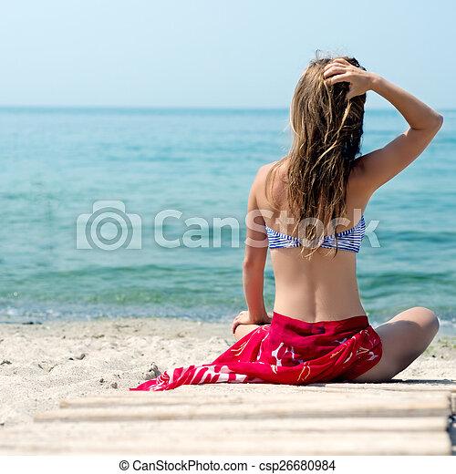 Una mujer camina por la playa - csp26680984