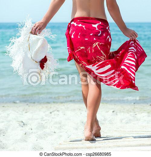 Una mujer camina por la playa - csp26680985