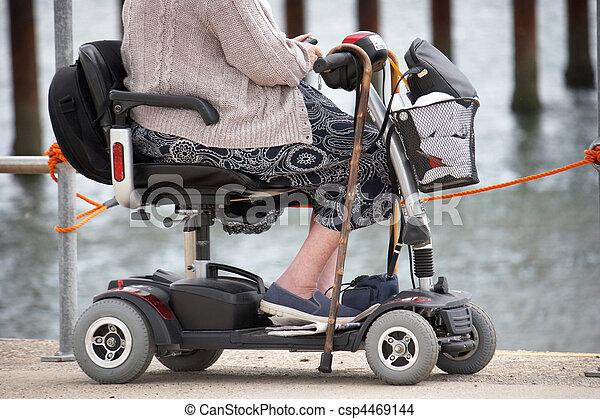 Una anciana en la playa en motoneta - csp4469144