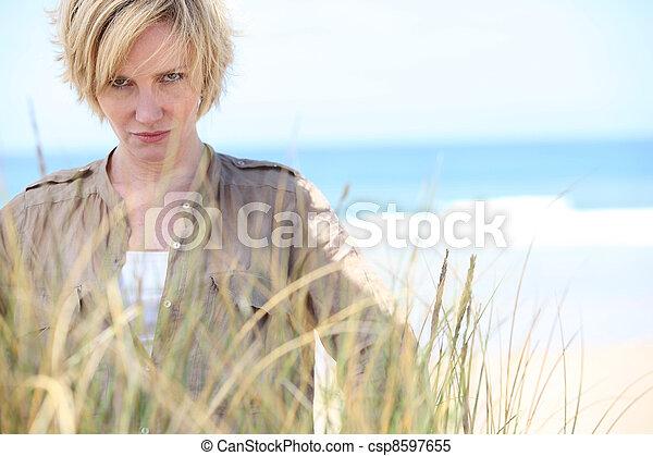 Mujer rubia con seria expresión en la playa - csp8597655