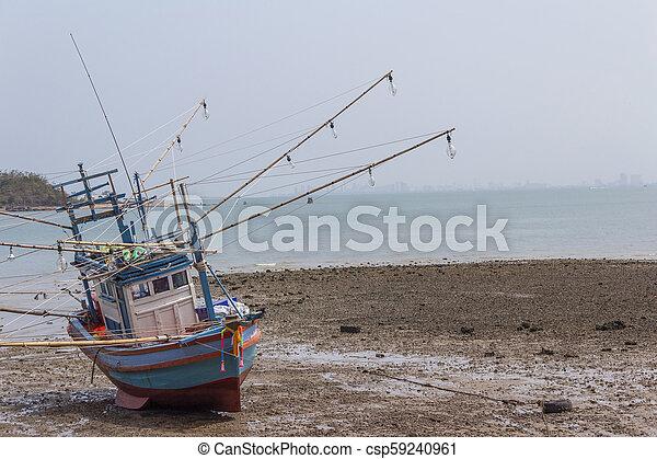 Un viejo barco de pesca estacionado en la playa. - csp59240961