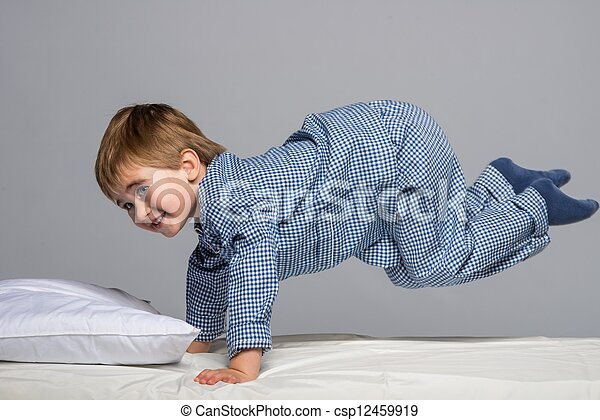 Playful little boy wearing blue pajamas in bed - csp12459919