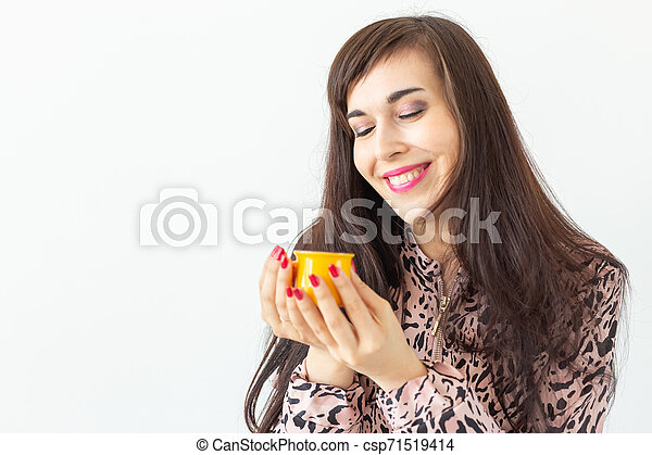 Playful young brunette woman holding in her hands a small yellow mug posing on a white background with copy space. Concept of morning coffee. - csp71519414