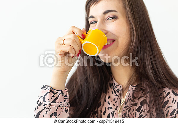Playful young brunette woman holding in her hands a small yellow mug posing on a white background. Concept of morning coffee. - csp71519415