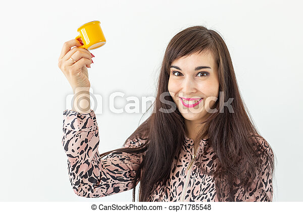 Playful young brunette woman holding in her hands a small yellow mug posing on a white background. Concept of morning coffee. - csp71785548