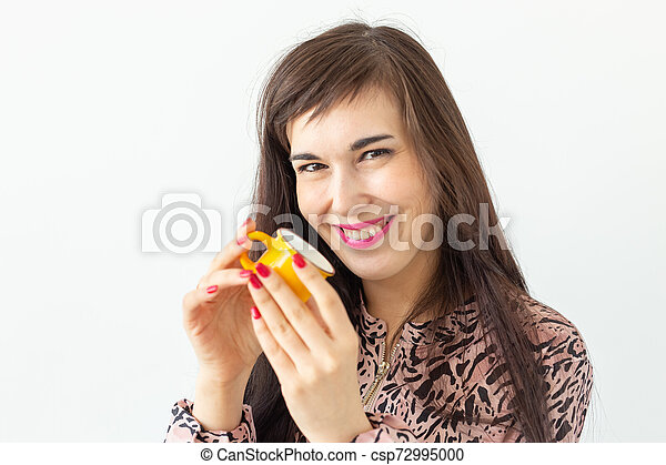 Playful young brunette woman holding in her hands a small yellow mug posing on a white background with copy space. Concept of morning coffee. - csp72995000