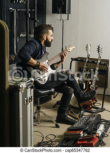 playing his electric guitar in the recording studio photo of a man with beard sitting and. Black Bedroom Furniture Sets. Home Design Ideas
