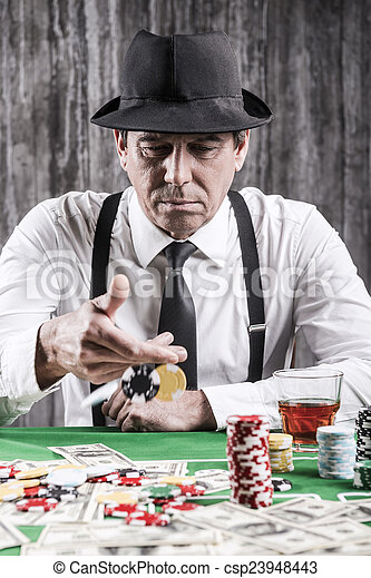 Playing poker. Serious senior man in shirt and suspenders throwing his gambling chips at the poker table  - csp23948443
